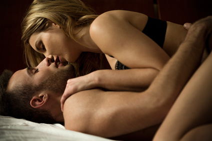 Young couple kissing passionately while lying in bed