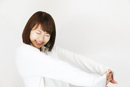背伸びをする若い女性