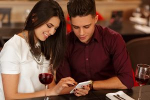 See this. Beautiful young dark haired woman smiling cheerfully showing something on her phone to her handsome boyfriend while on a date at the restaurant