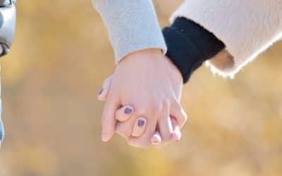 恋人つなぎのカップルの手