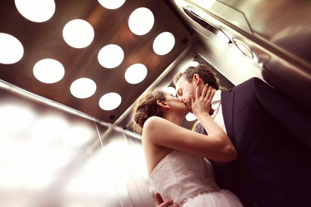 エレベーターの中でキスするカップル