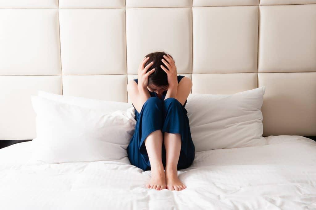 ベッドの上で三角座りをする女性