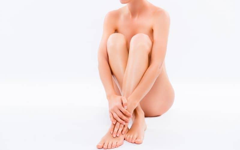 裸で膝をかかえて座る女性