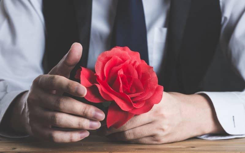 赤いバラの花を持っている男性