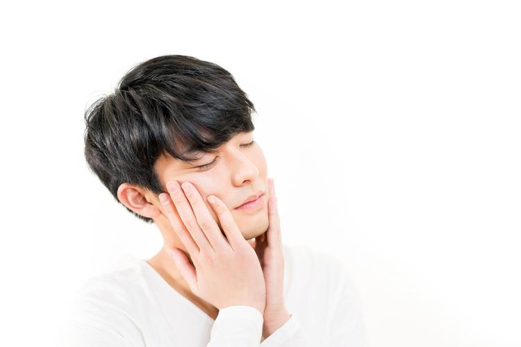 頬を触る男性