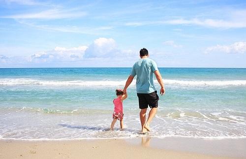 海辺で手を繋いで歩く親子