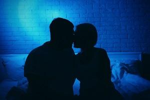 薄暗い部屋でキスするカップル