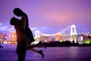 夜景をバックにハグするカップル